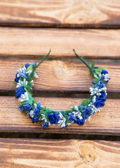 Handmade hoop blue flowers. Blue hair band on wooden background. Top view