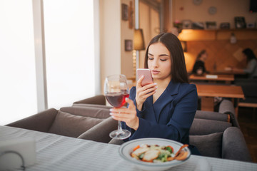 Beautiful young woman sit at table in restairant and take picture of glass red wine. Salad bowl stand in front of her.