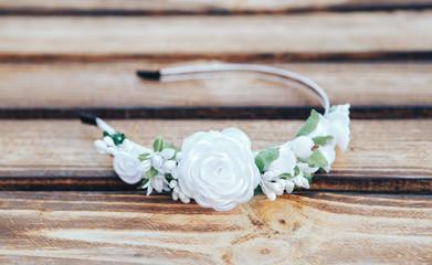 Handmade hoop white flowers. White hair band on wooden background