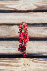 Handmade hoop flowers. Red poppies hair band on wooden background. Ukrainian style. Top view