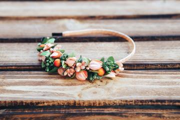 Handmade hoop flowers. Orange hair band on wooden background
