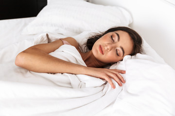 Image of brunette woman 20s with dark hair smiling, while lying and sleeping in bed on white linen