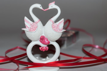 Two swans forming a heart and a gift in the background girdled with a red ribbon