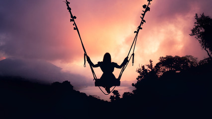 Girl on a swing in the clouds at sunset in the shade