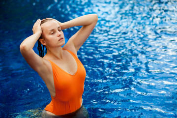 girl with wet hair swimming in the pool
