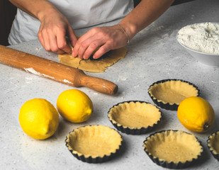 a process of making tartlets, female hands working with pastry dough