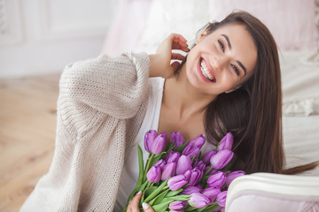 Close up portrait of young beautiful woman indoors. Attractive woman with flowers. Female with tulips. Spring bouquet.