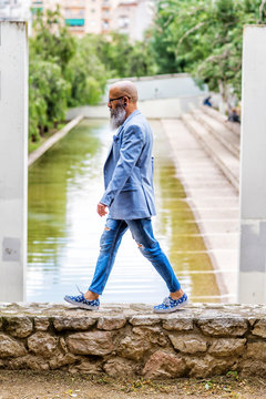 Side view of a hipster mature man wearing trendy attire while walking nest to a pond in a park
