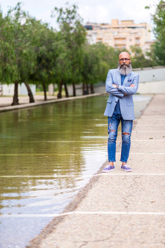 Front view of a hipster mature man wearing blue jacket standing next to a pond while looking camera