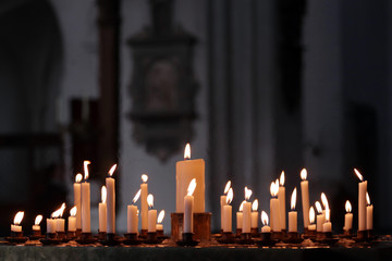 Many flames on candles lit in the church in respect. Christianity.