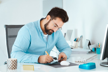 Young handsome businessman writing on paper at work office