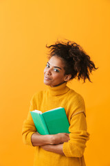 Cheerful african woman wearing sweater holding a book