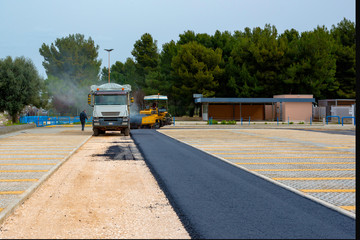Asphalt paver with asphalt heated to temperatures above 160 ° during road at the construction. Road specialized equipment is laying the way.