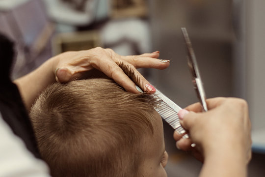 Little boy does a haircut at the hairdresser. Baby hair care.