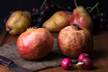 pomegranates and pears with other fruit bodegon with classic light on wood