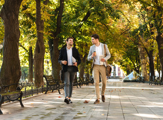Photo of young businessmen in suits walking outdoor through green park with takeaway coffee and laptop, during sunny day - fototapety na wymiar