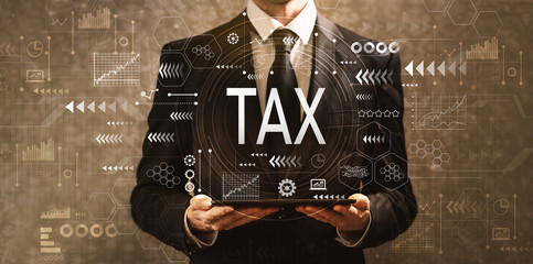 Tax with businessman holding a tablet computer on a dark vintage background