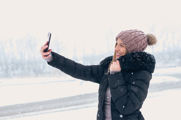Cheerful woman taking selfie outdoors in snow.