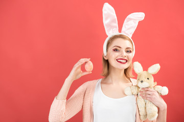 happy woman in bunny ears with toy. Spring holiday. Girl with hare toy. Woman in rabbit bunny ears. Happy easter. Egg hunt. Easter eggs as traditional food. Easter time. copy space