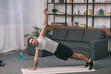 bi-racial man doing plank exercise on fitness mat in living room