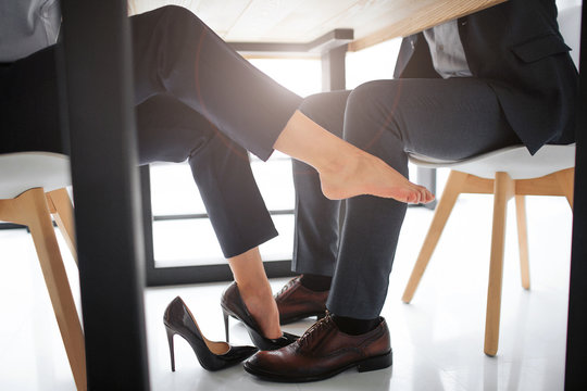Concept harassment. Cut view of young woman sit at table with man. Her right feet is without high-heels shoe. She touch man's leg. Picutr is very sexual.