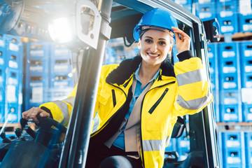 Arbeiter Frau fährt einen Gabelstapler in Logistik Lagerhaus