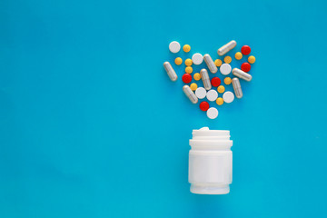 Pills heart out of pill bottle on blue background, top view