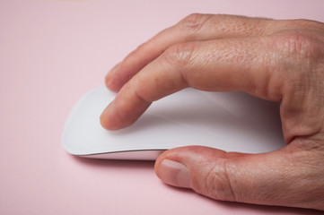 closeup of hand of man on white mouse on pink background