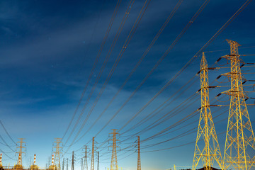 High voltage electric pole and transmission lines in the evening. Electricity pylons at night. Power and energy. Energy conservation. High voltage grid tower with wire cable at distribution station.