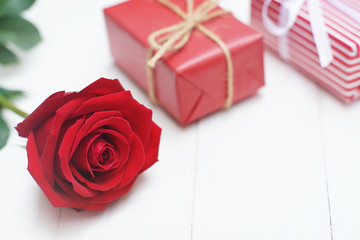 Lovely red color gift box decorated with mini red heart figure and beautiful rose flower, sweet valentine present concept, background and texture for valentine day