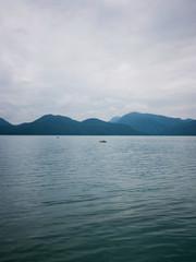 Boat far afield on a lake amid mountains