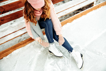 Woman tie shoelaces at figure skates at ice rink close-up, ice skating