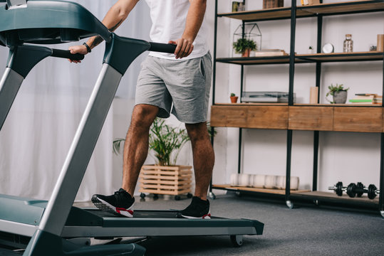 cropped view of man workout on treadmill in living room