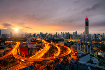 Wall Mural - Aerial view of Bangkok skyline panorama and skyscraper with light trails on expressway in center of business at capital city. Modern buildings condominium in Bangkok Thailand at sunrise.