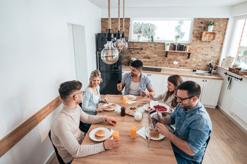 High angle image of friends eating homemade pancakes and having fun.