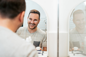 Handsome smiling man with anti-aging creme on his face in the bathroom.