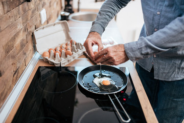 Man cooking eggs for breakfast, standing at the kitchen at home.
