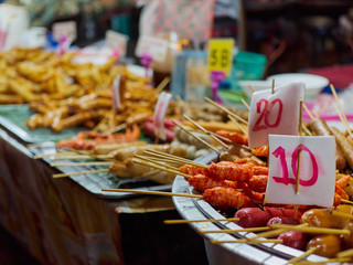 Street food. Various products (shrimps, sausages, etc.) are strung on wooden skewers and sold on the market. On the dishes set price tags