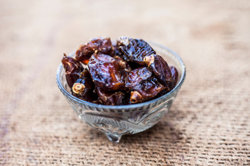 Close up of shot of raw organic dates or khajoor or Phoenix dactylifera in a glass bowl on a gunny bag background.