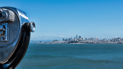 Popular observation point by the northern side of Golden Gate bridge, with cropped binoculars on the left, offering stunning vistas of the bay and the skyline of San Francisco city, California, USA
