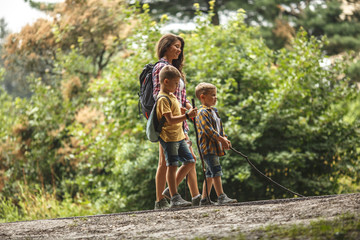 Mother and her little sons hiking trough forest .Outdoor spring leisure concept.