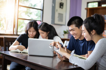 Group Students Smile and have fun and using tablet It also helps to share ideas in the work and project. And also review the book before the exam