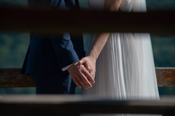 Cropped, paparazzi-style, private shot of young Caucasian bride and groom holding hands
