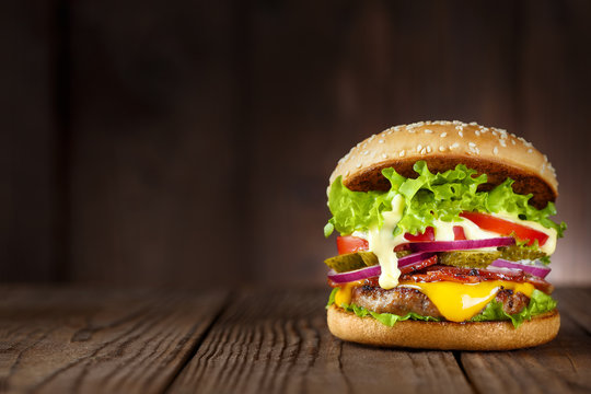 Delicious burger with bacon, cucumbers, lettuce, cheese, onion and tomatoes on dark wooden background
