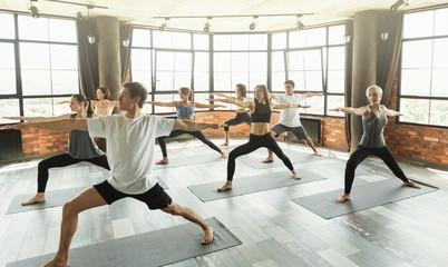 Millennials practicing yoga in a modern studio