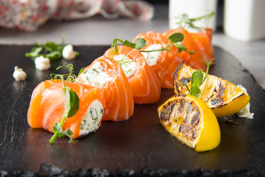 Salmon rolls stuffed with cream cheese and herbs, beautiful snack, elegant food for menu