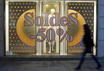A woman walks past a placard announcing a 50% discount on a clothing store's front window on the eve of the start of winter sales in Nice