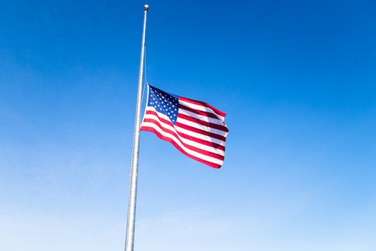 American flag at half mast against bright blue skies, signifying a day of mourning and remembrance in the United States.