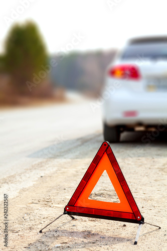 White Car And A Red Triangle Warning Sign On The Road