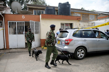 Kenyan police officers with dogs leave the scene where Chinese nationals were detained, after a police operation aimed at contraband goods including illegal ivory and animal trophies, in Kilimani area of Nairobi